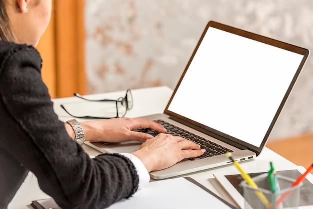Donkerbruine onderneemster die op laptop schrijft