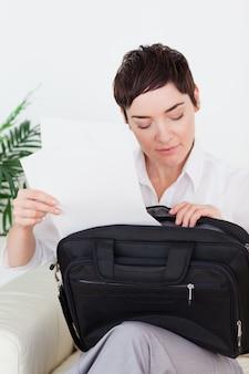 Donkerbruine onderneemster die sommige documenten in haar zak zet