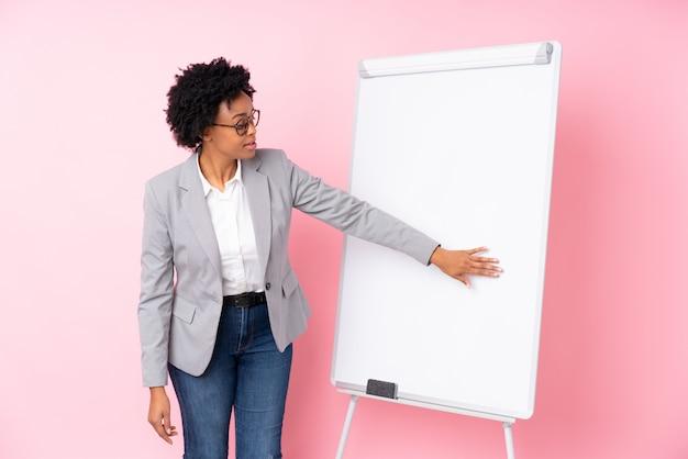 Donkerbruine onderneemster met whiteboard over geïsoleerde roze achtergrond