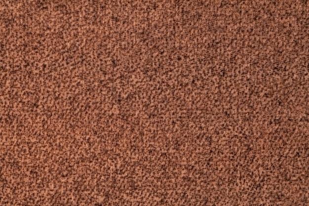 Donkerbruine pluizige achtergrond van zachte, veloursstof. textuur van omberwoltextiel