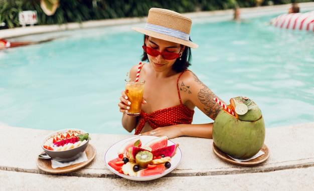 Donkerbruine tan vrouw in de rode zonnebril van kattenogen en strohoed het ontspannen in pool met plaat van exotisch fruit tijdens tropische vakantie. stijlvolle tatoeage.