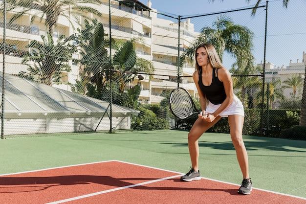 Donkerbruine tennisspeler die volledig schot opleidt