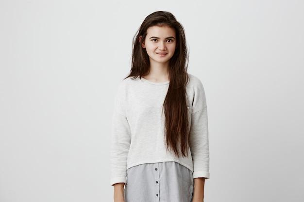 Donkerbruine tienervrouw die lang haar los in vrijetijdskleding draagt die vreugdevol glimlacht