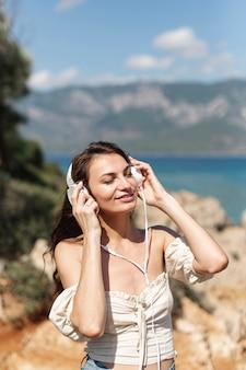 Donkerbruine vrouw die aan muziek luistert