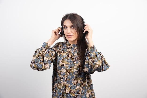Donkerbruine vrouw die aan muziek met ernstige uitdrukking luistert.
