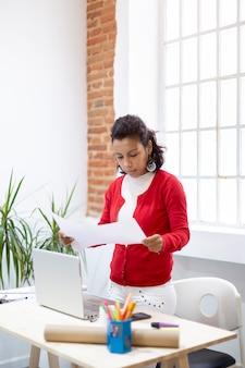Donkerbruine vrouw die bij haar bureau enkele documenten bekijkt. ruimte voor tekst. thuiskantoor concept.