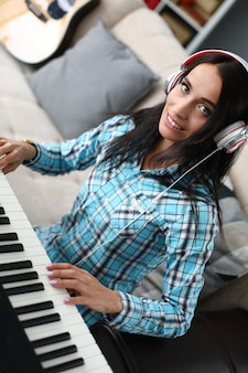 Donkerbruine vrouw die de piano met hoofdtelefoons speelt