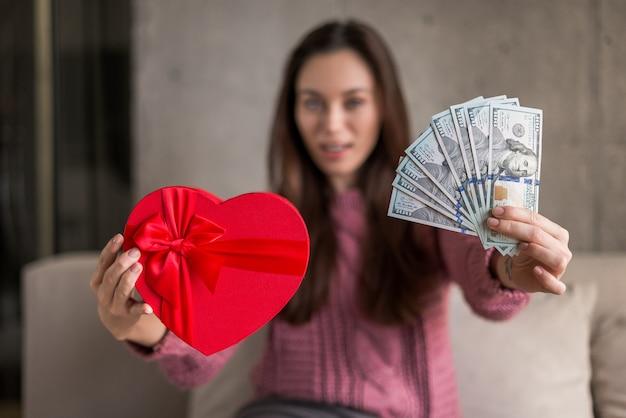 Donkerbruine vrouw die een hart-vormige doos en dollarrekeningen toont