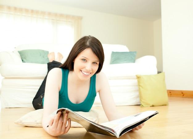 Donkerbruine vrouw die een tijdschrift leest die op de vloer ligt