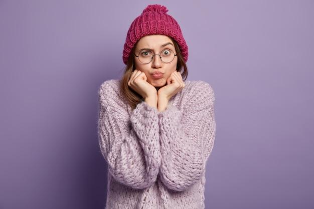 Donkerbruine vrouw die gebreide trui en muts draagt