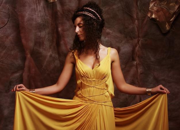 Donkerbruine vrouw die gele avondjurk draagt