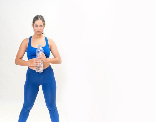 Donkerbruine vrouw die geschiktheid uitoefent om gewicht te verliezen en drinkwater in een fles