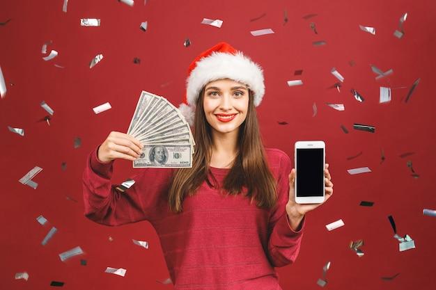 Donkerbruine vrouw die in kerstmishoed geld houdt en het apparaatscherm toont