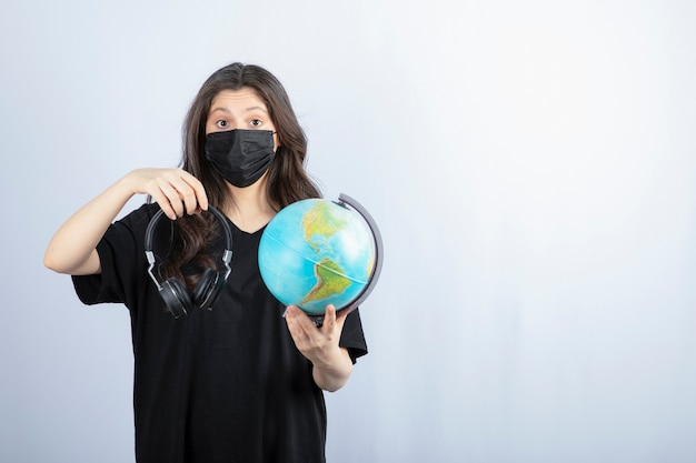 Donkerbruine vrouw die in medisch masker wereldbol met hoofdtelefoons houdt.