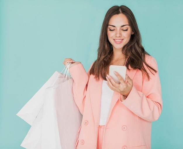 Donkerbruine vrouw die in roze jasje smartphone bekijken