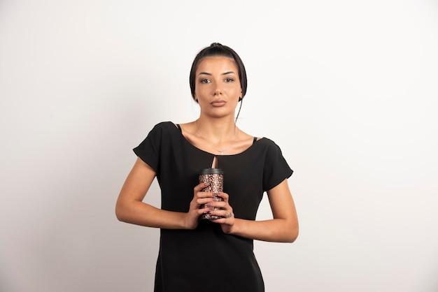 Donkerbruine vrouw die kop koffie stevig vasthoudt.