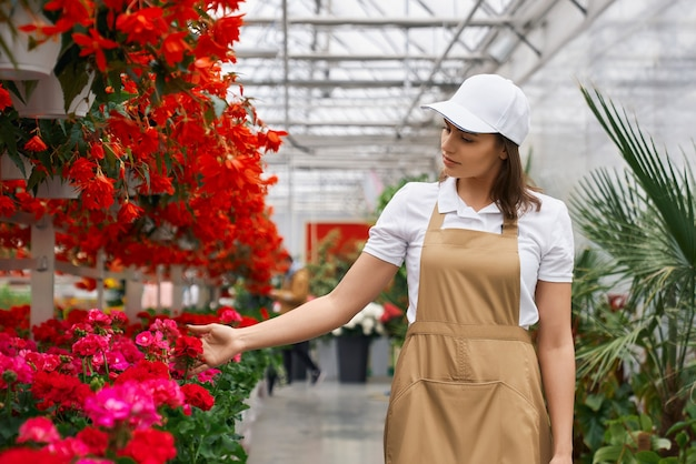 Donkerbruine vrouw die met bloemen in serre werkt