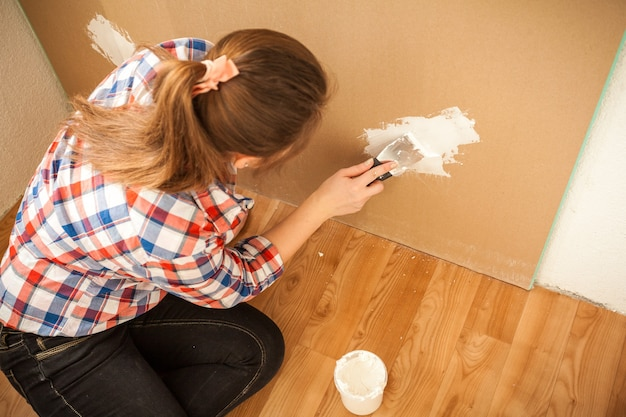 Donkerbruine vrouw die muur bij huis pleistert
