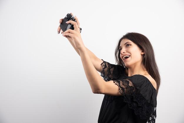 Donkerbruine vrouw die selfies met camera neemt