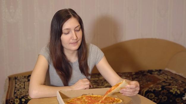 Donkerbruine vrouw die smakelijke pizza thuis eet.