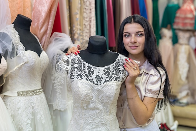 Donkerbruine vrouw die trouwjurk in salon bekijkt