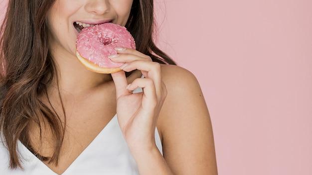 Donkerbruine vrouw die van een doughnut bijt