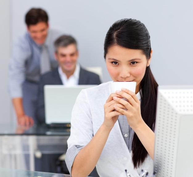 Donkerbruine vrouw het drinken koffie in het bureau