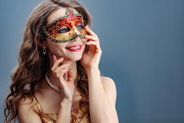 Donkerbruine vrouw in een kleurrijk carnaval-masker op een blauwe achtergrond die en omhoog glimlacht kijkt