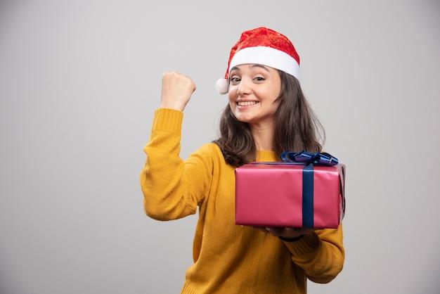 Donkerbruine vrouw in kerstmanhoed die haar vuist toont en giftdoos houdt.
