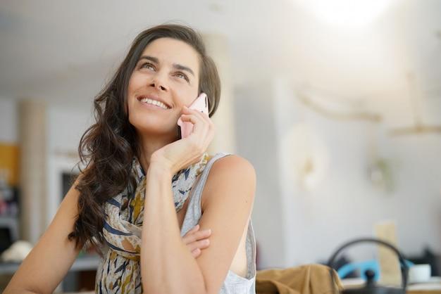 Donkerbruine vrouw in koffiewinkel die op telefoon spreekt
