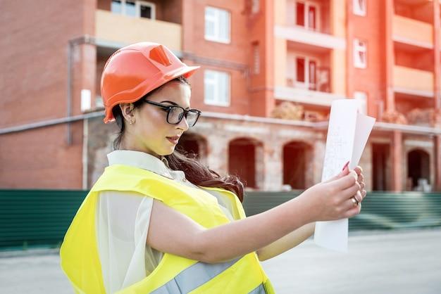 Donkerbruine vrouw in uniform die bouwplan onderzoekt
