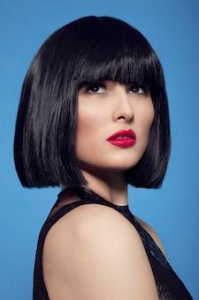 Donkerbruine vrouw in zwarte pruik met make-up en rode lippen, over blauwe achtergrond.