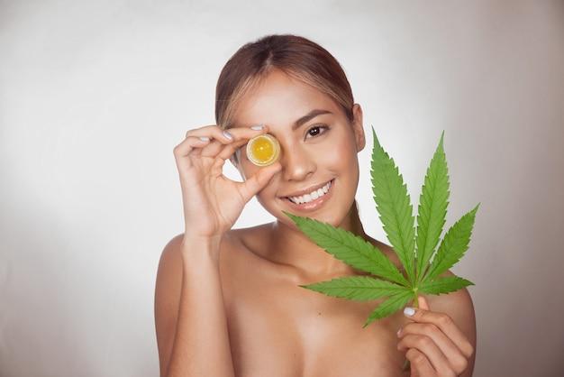 Donkerbruine vrouw met cbd-crème gemaakt van cannabisextract voor een natuurlijke behandeling. geïsoleerd op grijze achtergrond