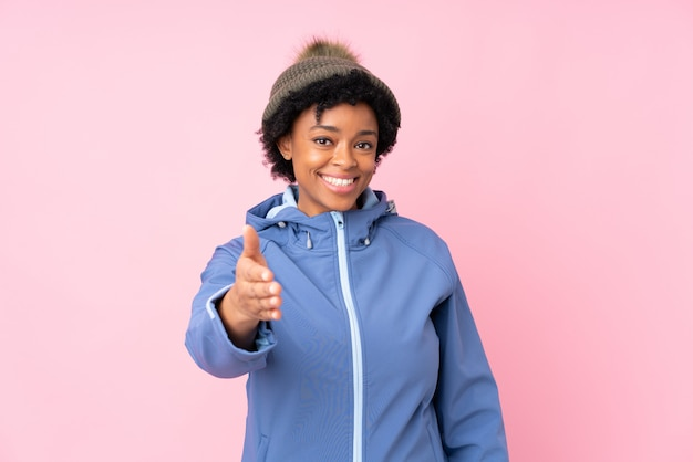 Donkerbruine vrouw met de winterhoed over geïsoleerde blauwe achtergrond