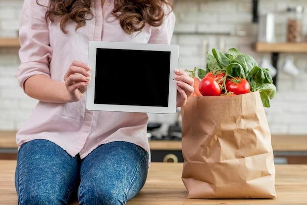 Donkerbruine vrouw met een document zakhoogtepunt van gezond voedsel