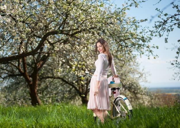 Donkerbruine vrouw met fiets die zich met haar terug bevindt en wendde zich tot de camera in een vers groen van de lentetuin.