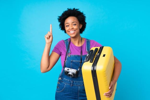 Donkerbruine vrouw met koffer over geïsoleerde blauwe achtergrond