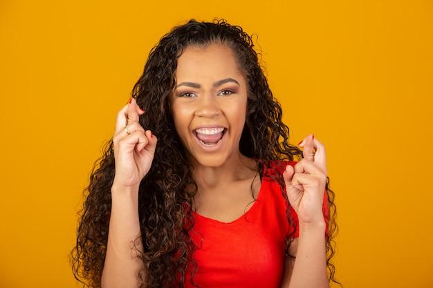 Donkerbruine vrouw met lang en glanzend krullend haar met haar gekruiste vinger