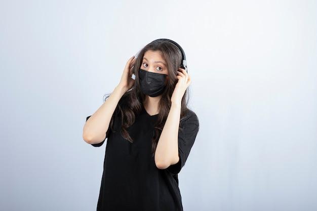 Donkerbruine vrouw met lang haar in medisch masker dat hoofdtelefoons draagt.
