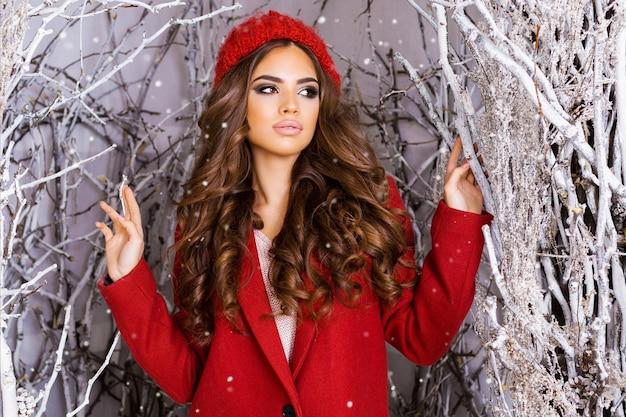 Donkerbruine vrouw met rode kleren onder besneeuwde bomen