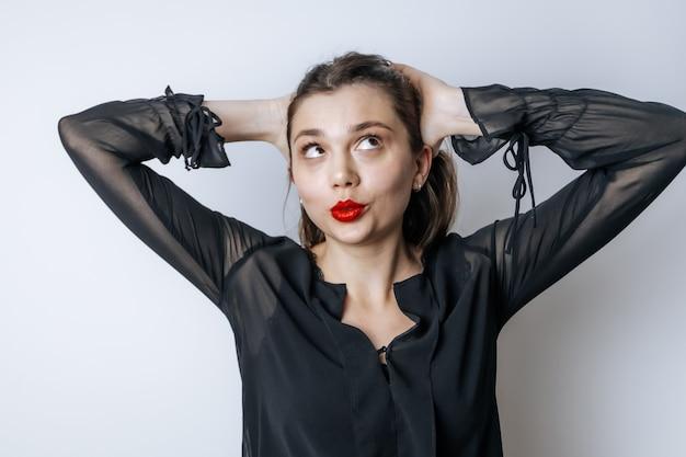 Donkerbruine vrouw met rode lippen raakt haar hoofd aan