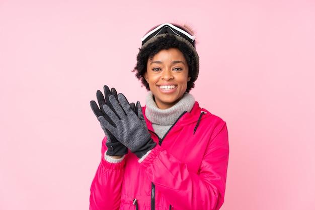 Donkerbruine vrouw met sneeuwglazen over geïsoleerde roze achtergrond