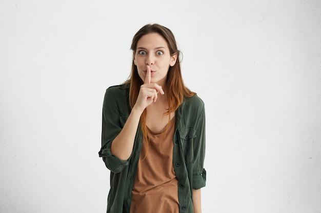 Donkerbruine vrouw met steil haar die groen jasje dragen die haar wijsvinger op lippen houden die stilte teken maken vragen om niet luidruchtig te zijn.