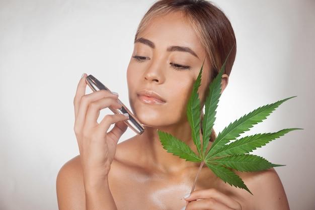 Donkerbruine vrouw met zwarte cbd-mascara gemaakt van cannabisextract voor een natuurlijke behandeling. geïsoleerd op grijze achtergrond