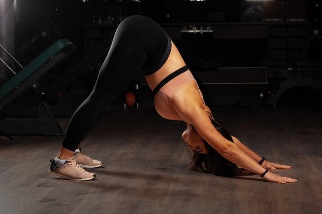 Donkerbruine vrouw plus groottemodel die rekoefeningen in een donkere gymnastiek doen