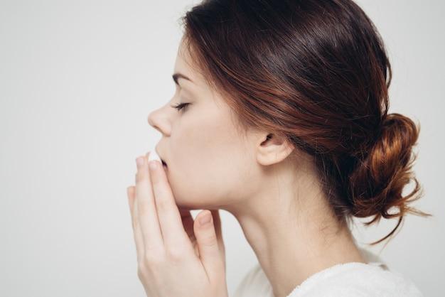 Donkerbruine vrouw veegt haar gezicht af met een witte spons op een licht
