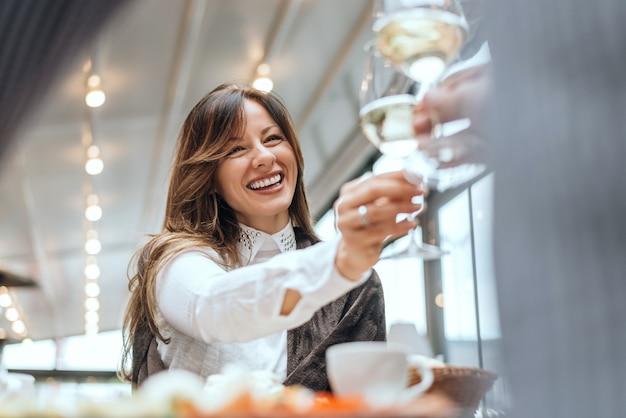 Donkerbruine vrouwen rammelende glazen met vriend in koffie.