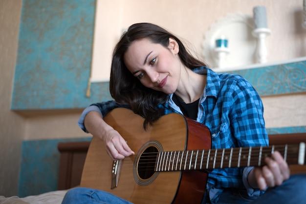 Donkerbruine vrouwenzitting op bed in de gitaar die van de slaapkamerholding een lied samenstelt - musicus, songwriterpt