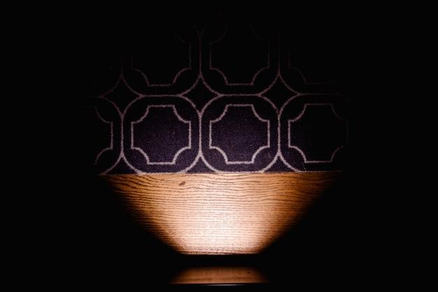 Donkere achtergrond die het vloertapijt verlicht door een lamp, exemplaarruimte.