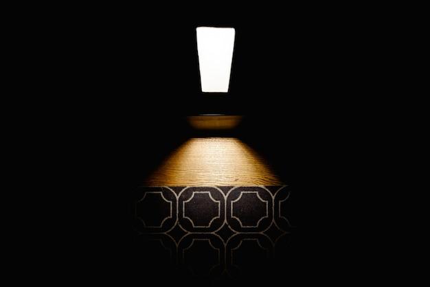 Donkere achtergrond die het vloertapijt verlicht door een lamp
